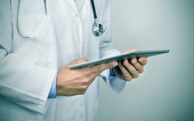 closeup of a young caucasian doctor man using a tablet computer